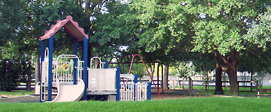 Playground toy with slides set in a park with trees and a fence.